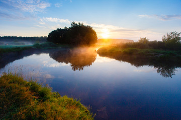 Summer peacefule sunrise on the river covered in fog. Blue sky above the tranquil countryside