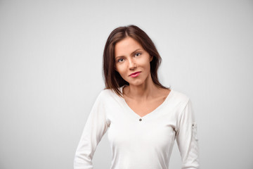 Pretty smiling joyfully female with dark hair, dressed casually, looking with satisfaction at camera, being happy. Studio shot of good-looking beautiful woman isolated against blank studio wall