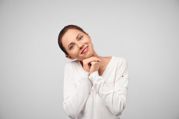Portrait of glad smiling female model leans at hands, has broad smile, happy to recieve compliments from handsome man, isolated over white background. Successful woman expresses pleasant feelings