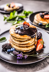 Pancakes with strawberries blackberries blueberries and lavender.