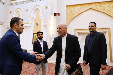 Afghan President Ashraf Ghani shakes hands with media before a news conference in Kabul