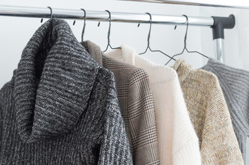 Winter wardrobe showcase. White and gray tone knitwear hanging on a clothes rack. Selective focus, horizontal