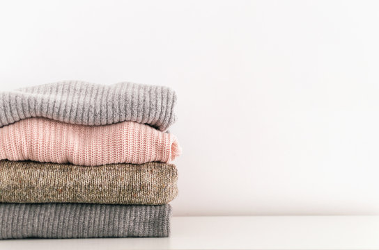 Stack of neatly folded knitwear. Minimal lifestyle, capsule wardrobe. Detail of cozy winter interior