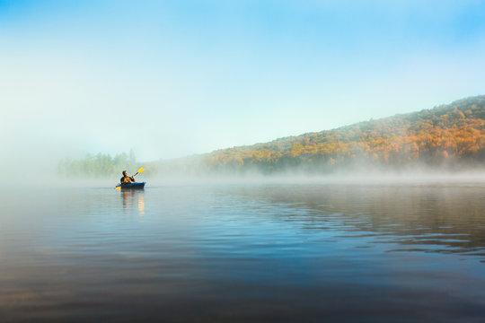 Acive Senior Man Solo Kayaking in Morning
