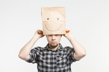 Sad men taking off happy paper mask on white background