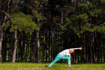 Redhead girl doing Yoga in the park