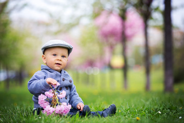 Portrait of cute stylish smiling toddler boy sitting n the grass in park outdoors