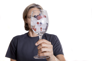 Woman holding glass with ice and berries.  Isolated on white background.