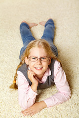 school age girl with glasses on a carpet