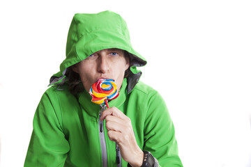 Woman with green jacket and hood eating a colorful sucker.