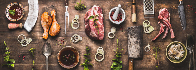 Flat lay of various grill and bbq meat : chicken legs, steaks, lamb ribs with vintage kitchenware kitchen utensils:  Meat Fork and Butcher Cleaver and herbs knife. Sauces and ingredients for grilling,