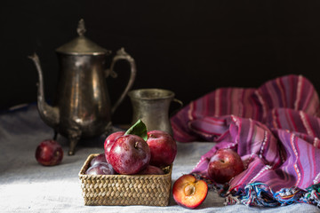 Fresh plum. Autumn harvest. Red plums. Yellow plum. Fresh plums on a wooden surface. Fresh plums on wooden table background with napkin and vintage kettle and glass. Bronze ware.