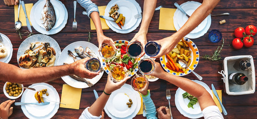Big family dinner. Vertical top view on served table and hands with clinking goblets