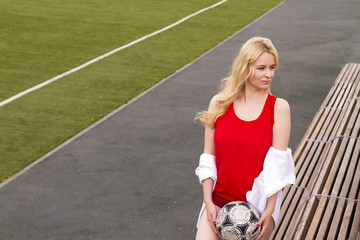 Blonde with a ball on the football field in red uniform.