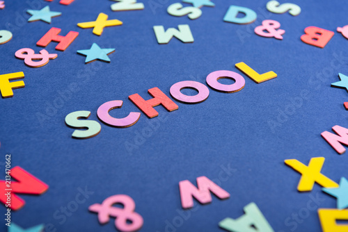 Colorful word SCHOOL on mixed English alphabets background