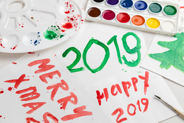 Children's drawings set by a watercolor on white paper of a congratulation by New year and Christmas. Figure 2019 largely green paint. A palette and a set of paints on a table. Horizontal shot