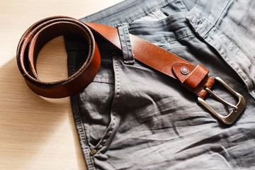 Male jeans and leather belt on wooden background