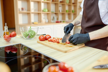 Closeup of unrecognizable male chef cutting vegetables standing at wooden table in restaurant kitchen, copy space