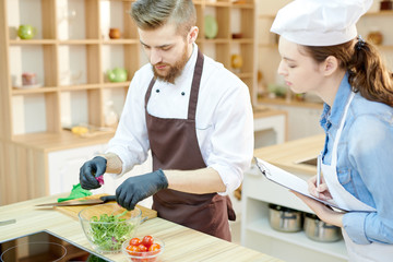 Portrait of two professional chefs working in restaurant kitchen together cooking and seasoning salad standing at wooden table