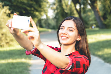 Portrait of a beautiful brunette girl in a red, plaid shirt, taking selfie, video chatting
