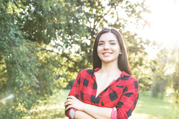 Smiling beautiful brunette girl in a red, plaid shirt, with arms crossed