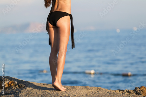 4bff15e46a close up young slim shapely beauty legs, woman in black bikini on sunset  beach. concept of beautiful healthy tan