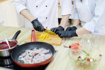 Close up of two unrecognizable  chefs cooking dishes in frying pan while working in modern restaurant kitchen
