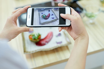 Close up of unrecognizable woman holding smartphoneand taking picture of delicious dish in restaurant, focus on screen