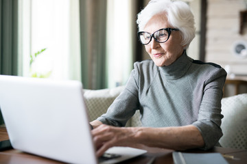 White haired senior woman wearing eyeglasses sitting at cafe and using her laptop