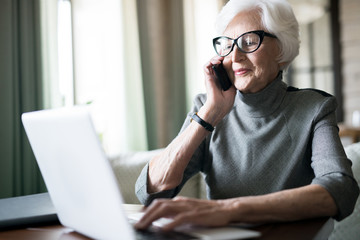 Elegant senior woman with white hair typing on laptop during conversation on telephone working distanly in cafe