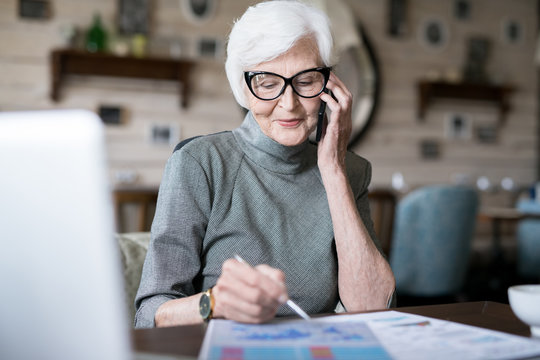 Elder lady with white haired planning her work while talking on cellphone
