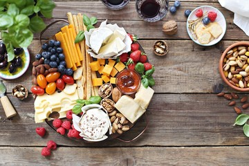 Spoed Fotobehang Voorgerecht Cheese platter with fresh berries and nuts on a rustic wooden table. Overhead view.