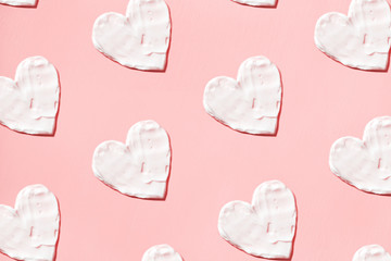 Hearts pattern from cream in pink background. Skin care