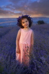 Cute beautiful girl in pink dress and flower crown posing at lavender field at sunset