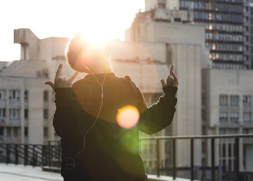 Man in the headphones looking up, showing shaka sign, Sunset, sunny beams.