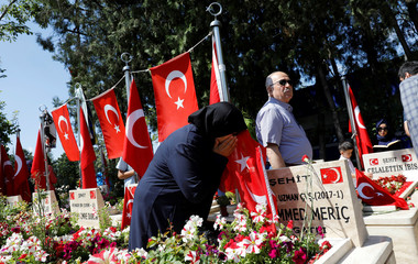 A woman mourns as she visits her son's grave who was killed during an attempted coup in 2016 as she attends a ceremony marking the second anniversary of the failed coup in Ankara