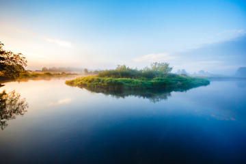 Summer morning landscape in the picturesque countryside. Colorful sunrise by the foggy river