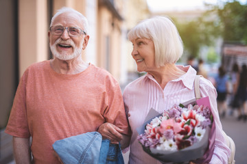 Waist up portrait of smiling mature male walking with woman on street.  They are joyfully talking while strolling side by side