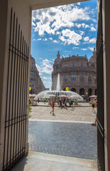 GENOA (GENOVA), ITALY, JULY, 7, 2018 - View of the fountain of  De Ferrari Square through a gate in the heart of cityof Genoa (Genova), Italy.