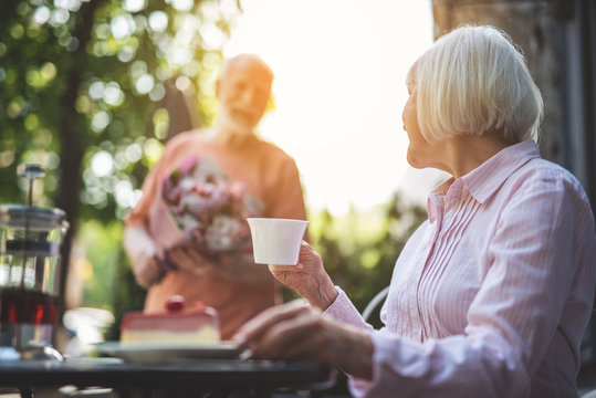 Pleasant expectation. Focus on side view of mature woman sitting at table with cup of tea in hand and turning sideways. Senior male with bunch of flowers is coming over joyfully