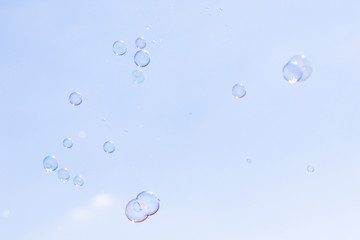 Soap bubbles in flight against the blue sky