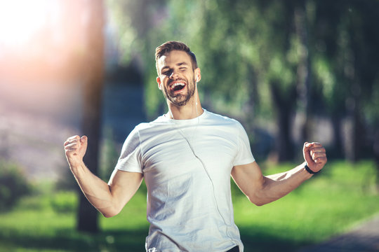 It is my life. Waist up portrait of smiling young man singing with earphones during jogging. He is clenching fists with delight and closing eyes in joy