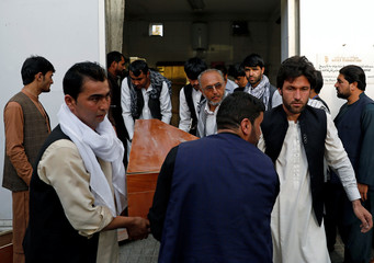 Relatives carry a coffin of a victim at a hospital after a blast in Kabul