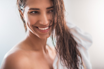 Portrait of satisfied female with brilliant smile keeping hair with towel