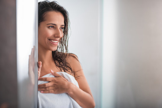 Portrait of satisfied woman with wet hair situating indoor after bath