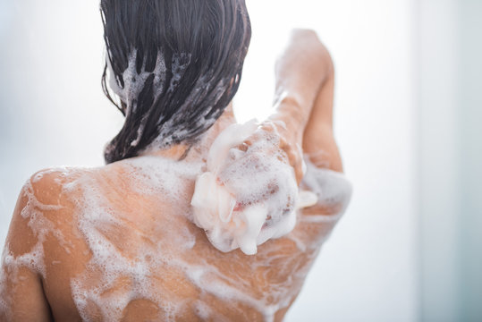 Young lady with smooth skin taking shower with flavorous gel while turning back to camera