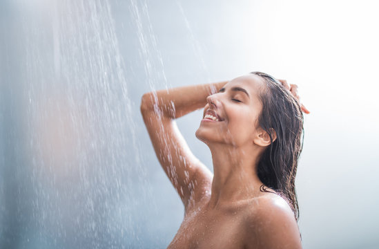 Side view happy woman washes body and hair under stream of hot water