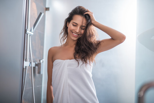 Portrait of outgoing woman standing after taking bath. She holding hair with hand