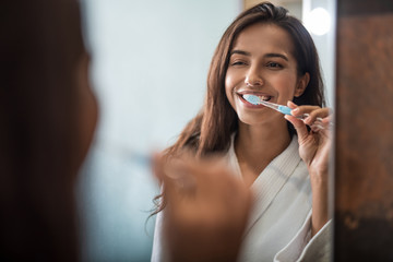 Portrait of beaming pretty woman brushing teeth while looking at mirror