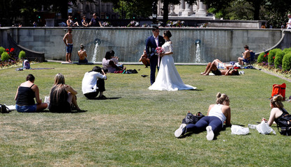 A bride and groom pose for photographs in a Garden next to St Paul's Cathedral, in central London,